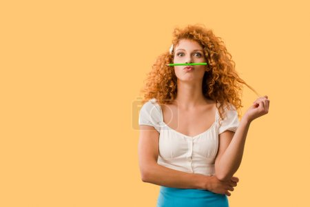 Photo for Beautiful redhead woman with pencil isolated on yellow - Royalty Free Image