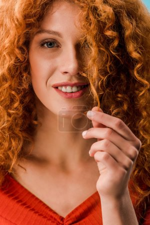 Photo pour Portrait de belle femme retenant le cheveu bouclé rouge - image libre de droit