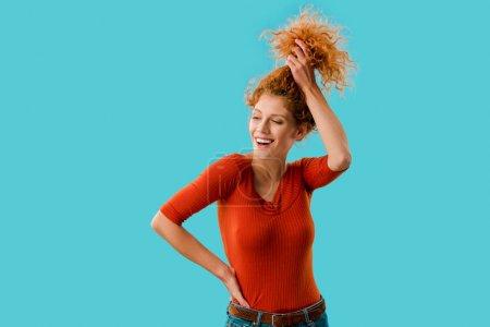 Photo pour Belle fille souriante tenant les cheveux bouclés rouges isolés sur bleu - image libre de droit