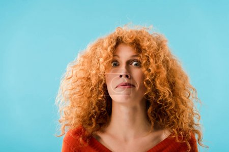 Photo for Portrait of shocked redhead woman isolated on blue - Royalty Free Image