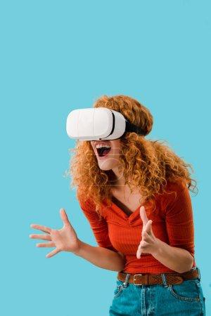 Photo pour Femme émotionnelle criant dans casque de réalité virtuelle isolé sur bleu - image libre de droit