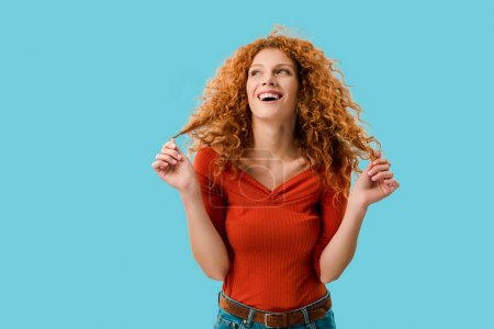 Photo for Portrait of laughing redhead girl isolated on blue - Royalty Free Image