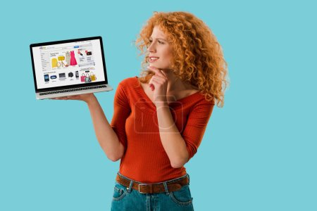 Photo for KYIV, UKRAINE - JULY 16, 2019: pensive redhead woman holding laptop with ebay website, isolated on blue - Royalty Free Image