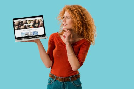 Photo pour Kiev, Ukraine - 16 juillet 2019: femme rousse pensive tenant ordinateur portable avec site depositphotos, isolé sur le bleu - image libre de droit