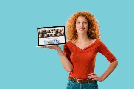 Photo pour Kiev, Ukraine - 16 juillet 2019: femme rousse souriante tenant l'ordinateur portatif avec le site Web de depositphotos, isolé sur le bleu - image libre de droit