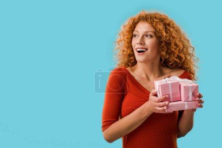 Photo pour Femme heureuse tenant des cadeaux isolés sur bleu - image libre de droit