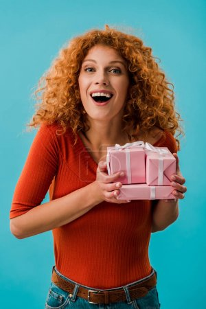beautiful excited girl holding gifts isolated on blue