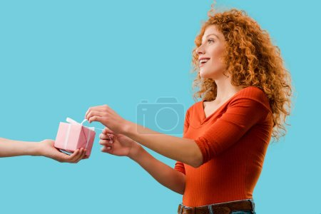 Photo for Beautiful happy redhead woman taking present isolated on blue - Royalty Free Image