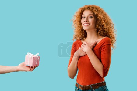happy redhead woman with gift box isolated on blue