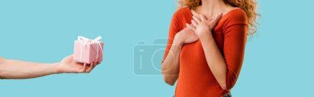abgeschnittene Ansicht der rothaarigen Frau mit Geschenkbox isoliert auf blau
