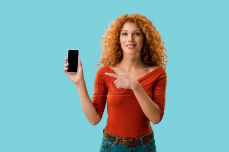 curly smiling woman pointing at smartphone with blank screen isolated on blue