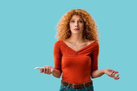 Photo for Curly confused woman holding smartphone isolated on blue - Royalty Free Image