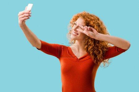 Photo pour Femme rousse bouclée avec symbole de paix prenant selfie sur smartphone isolé sur bleu - image libre de droit