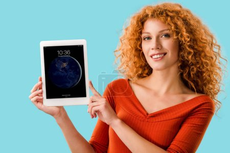 Photo for KYIV, UKRAINE - JULY 16, 2019: smiling redhead woman holding digital tablet with ipad, isolated on blue - Royalty Free Image