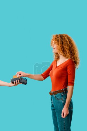 Photo for Curly redhead woman paying with credit card on terminal, Isolated On blue - Royalty Free Image