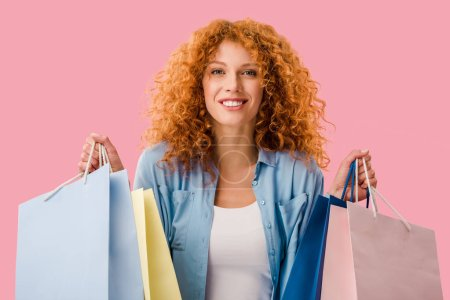Photo for Beautiful happy girl holding shopping bags, Isolated On pink - Royalty Free Image