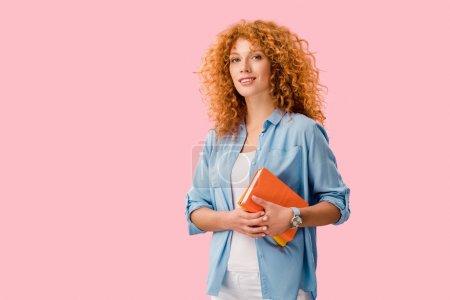 Photo pour Beau étudiant heureux tenant des livres isolés sur rose - image libre de droit