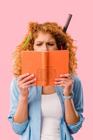 Photo pour Étudiante concentrée avec crayons dans un livre de tenue de cheveux isolé sur rose - image libre de droit