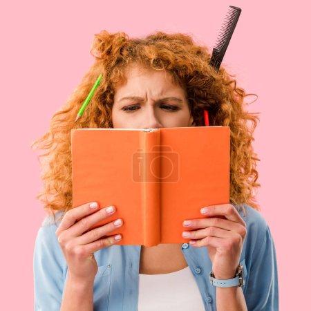 Photo pour Étudiant concentré avec des crayons dans le livre de tenue de cheveux isolé sur rose - image libre de droit