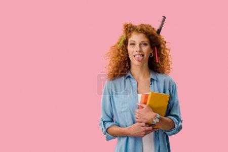 Photo pour Étudiant de rousse avec des crayons dans des livres de fixation de cheveux et langue collante dehors d'isolement sur le rose - image libre de droit