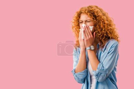 Photo pour Malade rousse femme éternuer avec des serviettes en papier, isolé sur rose - image libre de droit