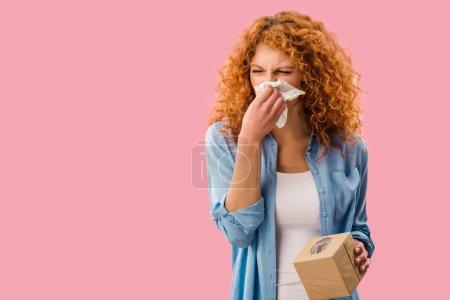Photo pour Rousse femme pleurer avec des serviettes en papier, isolé sur rose - image libre de droit