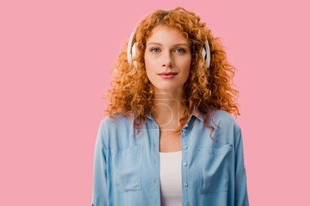 Foto de Atractiva mujer pelirroja escuchando música en auriculares, Aislado en rosa - Imagen libre de derechos