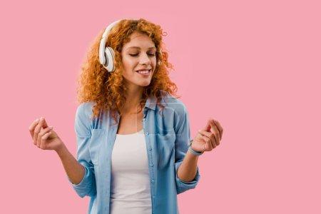Photo pour Femme bouclée écouter de la musique dans les écouteurs, isolé sur rose - image libre de droit