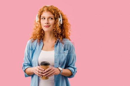 Photo pour Rousse femme avec café pour aller écouter de la musique dans les écouteurs, isolé sur rose - image libre de droit