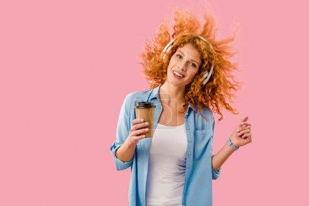 Photo pour Femme heureuse avec le café pour aller danser et écouter la musique dans le casque, isolated on rose - image libre de droit