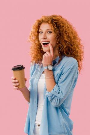 Foto de Excitado hermosa mujer rizada con el pelo rojo sosteniendo el café para ir, aislado en rosa - Imagen libre de derechos