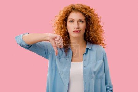 Foto de Pelirroja mostrando el pulgar hacia abajo aislado en rosa - Imagen libre de derechos