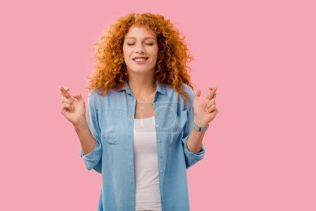 Photo pour Gaie rousse fille avec les yeux fermés croisant ses doigts isolés sur rose - image libre de droit