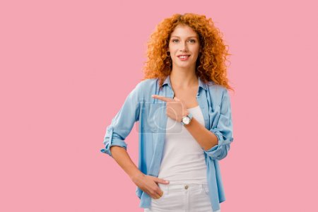 Photo pour Attrayant rousse jeune femme pointant isolé sur rose - image libre de droit
