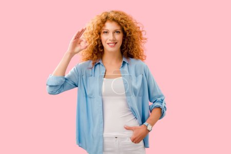 Photo pour Heureux attrayant rousse fille montrant ok signe isolé sur rose - image libre de droit