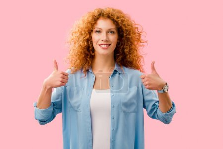 Photo pour Attrayant rousse fille montrant pouces jusqu'à isolé sur rose - image libre de droit
