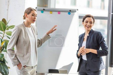 Photo pour Deux femmes d'affaires souriantes dans l'usure formelle restant près de flipchart dans le bureau - image libre de droit