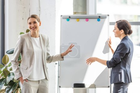 Photo for Two smiling businesswomen in formal wear standing near flipchart in office - Royalty Free Image