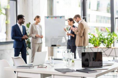 Photo pour Foyer sélectif de quatre hommes d'affaires multiethniques près de tableau à feuilles mobiles et table avec des ordinateurs portables et des verres d'eau au premier plan - image libre de droit