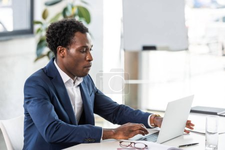 Photo for Focused african american businessman in formal wear using laptop in office - Royalty Free Image
