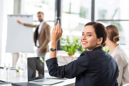 Photo for Smiling businesswoman raising hand during conference in office - Royalty Free Image