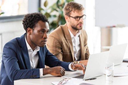 Photo pour Deux hommes d'affaires multiethniques utilisant des ordinateurs portables à la table dans le bureau - image libre de droit