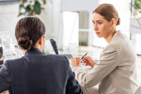 Photo pour Deux femmes d'affaires en tenue formelle se regardant dans le bureau - image libre de droit