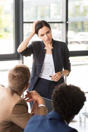 Photo pour Femme d'affaires pensive restant près des collègues et touchant la tête - image libre de droit