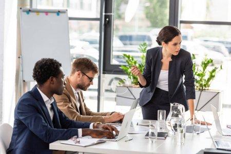Photo pour Hommes d'affaires multiethniques assis à des tables pendant la conférence dans le bureau - image libre de droit