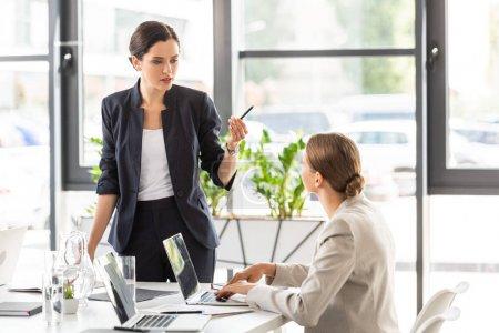 Photo pour Deux femmes d'affaires en tenue formelle se regardant et parlant dans le bureau - image libre de droit