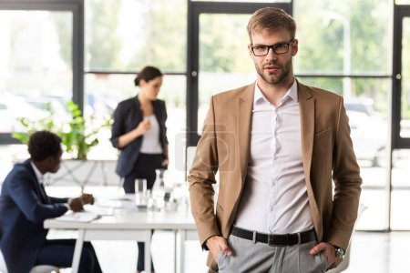 front view of office worker in glasses standing with hands in pockets and looking at camera