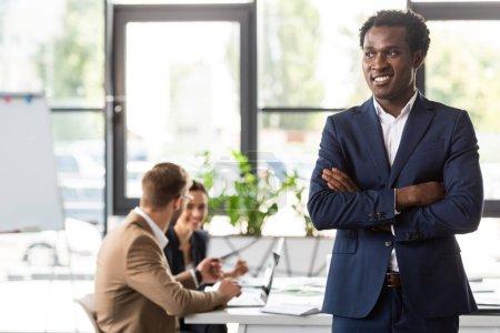 Photo pour Homme d'affaires américain africain de sourire dans l'usure formelle restant avec les bras croisés devant des collègues dans le bureau - image libre de droit