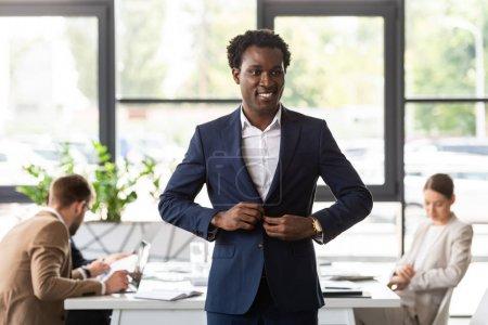Foto de Sonriente hombre de negocios afroamericano en ropa formal de pie frente a colegas en la oficina - Imagen libre de derechos