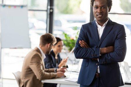 Foto de Sonriendo hombre de negocios afroamericano de pie con los brazos cruzados en la oficina - Imagen libre de derechos